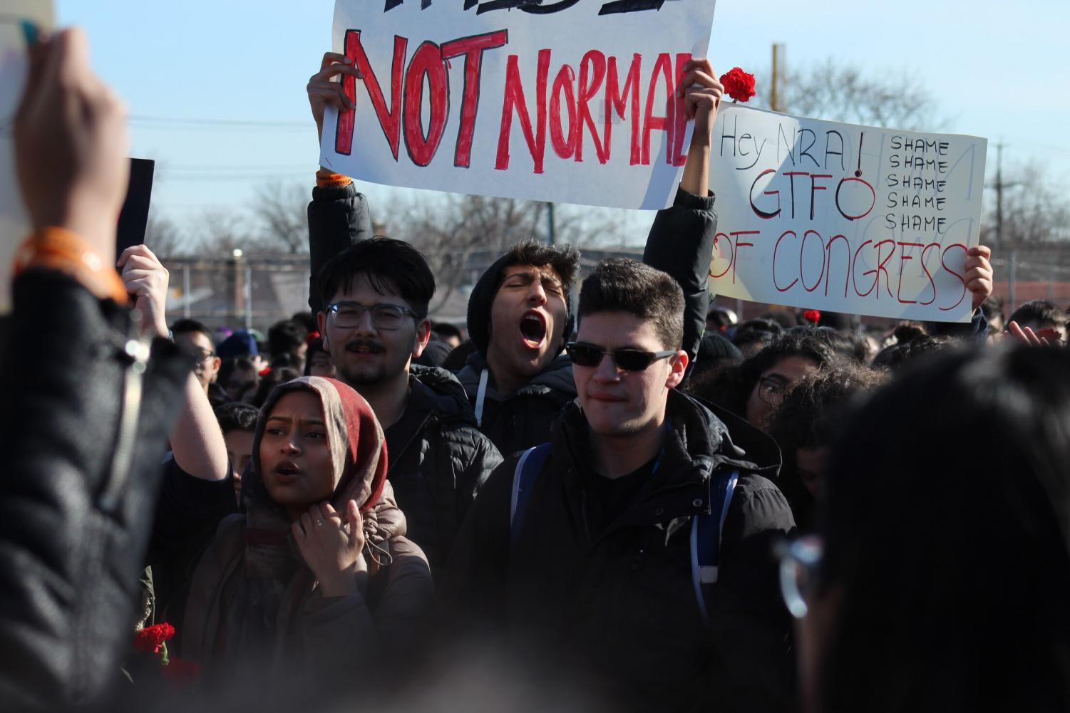 Francis+Lewis+alumnus+Joseph+Salvatore+holds+up+a+%22Not+Normal%22+sign+while+protesting+at+the+National+School+Walkout.