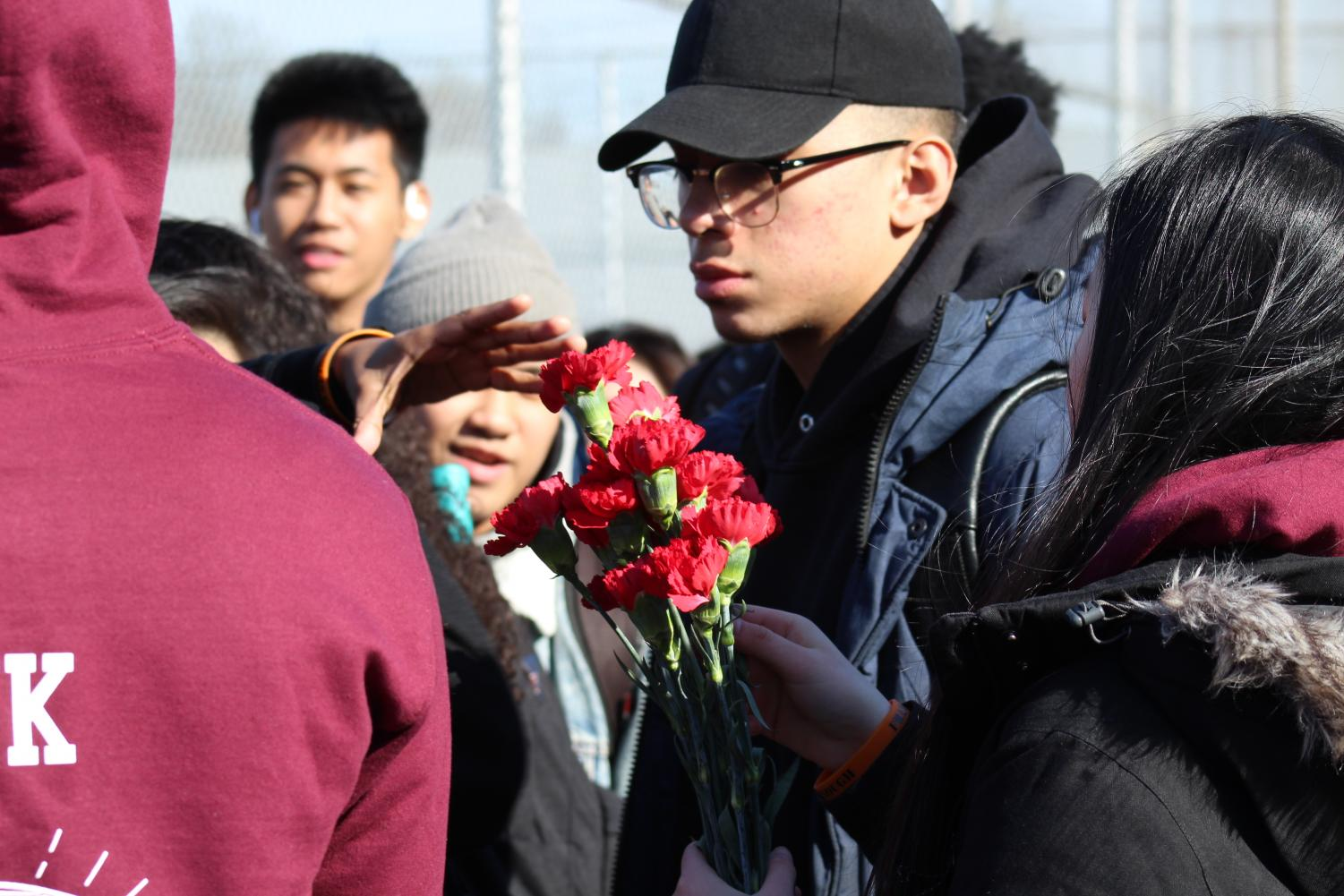 Students+distributed+red+carnations+in+honor+of+the+Parkland+victims.