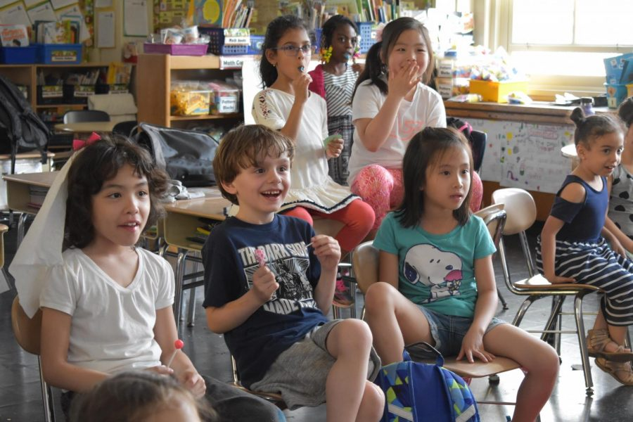 Elementary school students burst out in laughter as high school volunteers entertain them with an educational presentation about kindness.