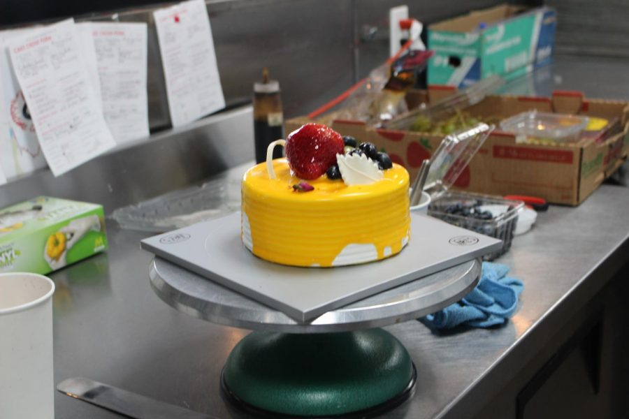 Tasty peach and mango cake with a finishing touch of fresh berries on top waits to be brought out. A happy customer will take it home.