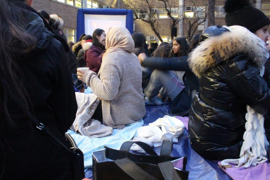 Students chatting with their friends while wrapped in blankets.