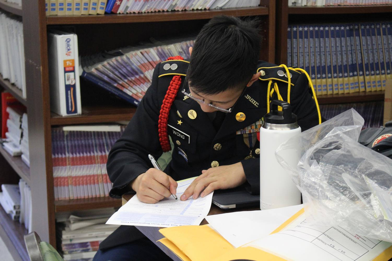 A+senior+and+JROTC+student+completes+a+voter+registration+form.+