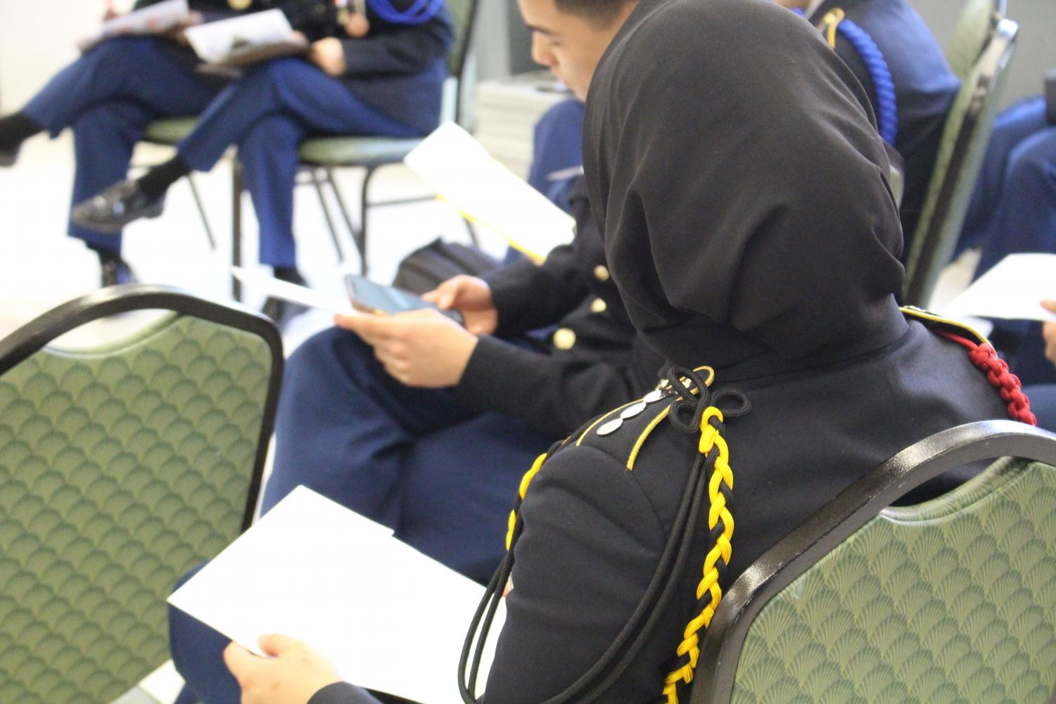 A+senior+and+JROTC+member+listens+to+registration+instructions+while+examining+the+voting+form.