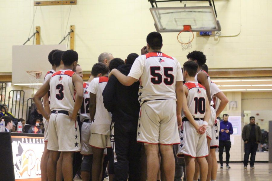 Francis+Lewis+Patriots+salute+Coach+Little+in+their+team+huddle+during+a+timeout.+